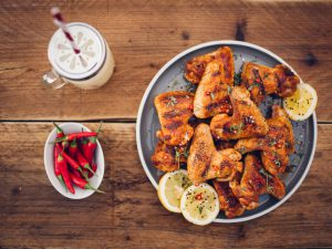 Overhead shot of a plate of spicy chicken wings with a bowl of fresh red chillies and a summer beverage on a vintage wooden surface