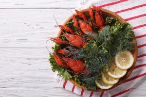 crayfish with fresh herbs and lemon on wooden plate. Horizontal top view